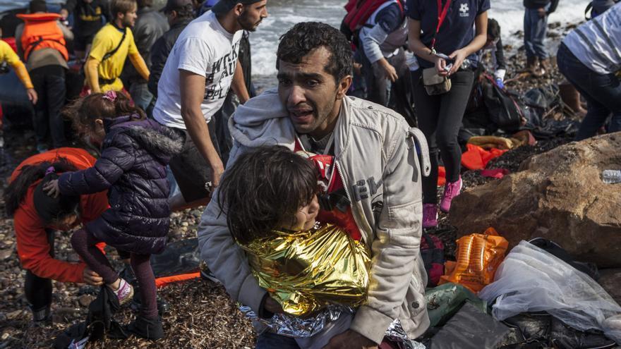 Cientos de refugiados lograron tocar tierra tras el naufragio de una embarcación en Lesbos. En la foto, un padre con su hija  / Santi Donaire