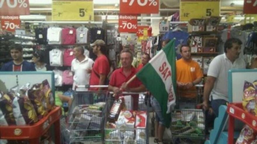 Dirigentes del SAT con carros de comida para llevarlos a un banco de alimentos