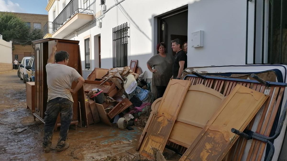 Vecinos de una calle de Lepe con todo lo que han perdido en la puerta de su casa.