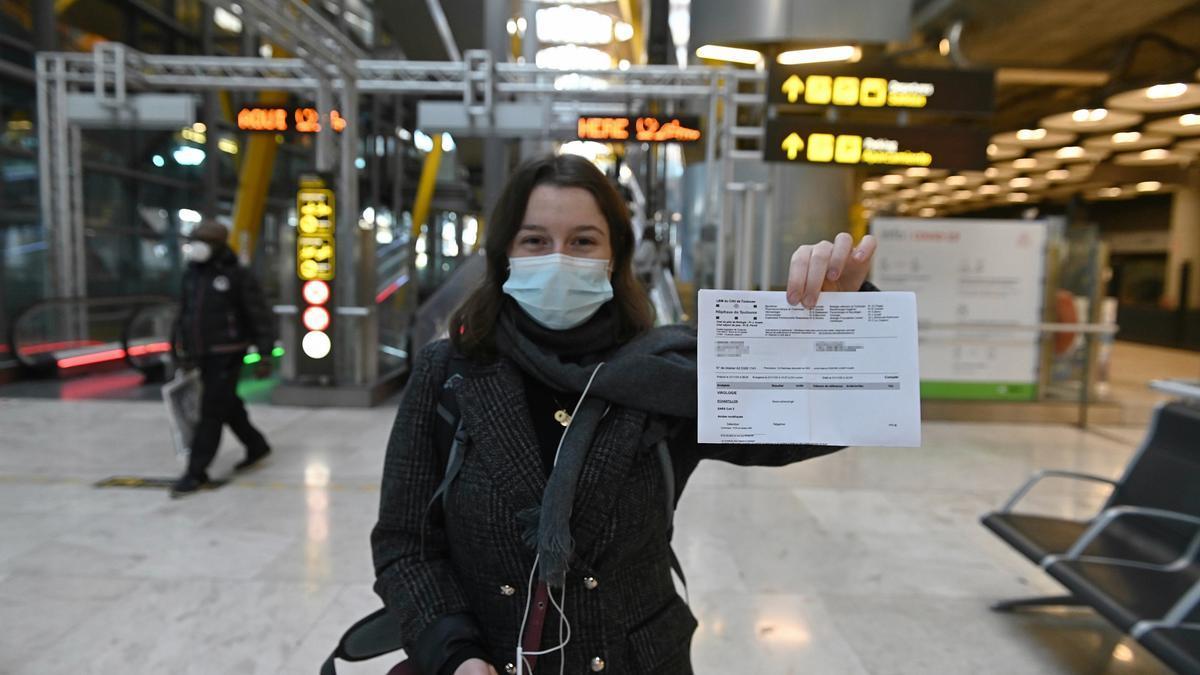 Una joven muestra el resultado de su PCR a su llegada al aeropuerto Adolfo Suárez-Barajas en Madrid