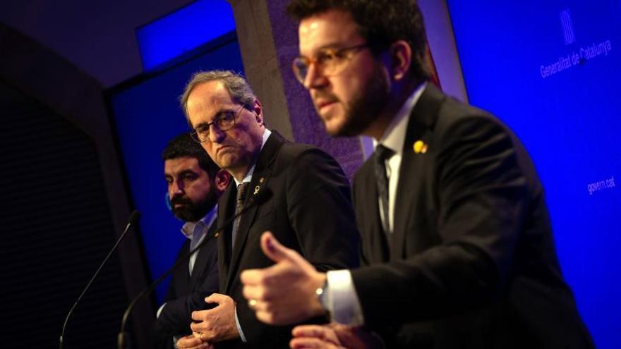 El presidente de la Generalitat, Quim Torra (c), junto con su vicepresidente, Pere Aragonès (d), y el conseller de Trabajo, Chakir El Homrani (i), durante una rueda de prensa.