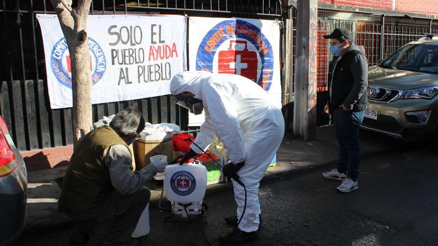 Voluntarios del Comité de Emergencia del barrio La Granja desinfectan las calles y casas en Santiago de Chile