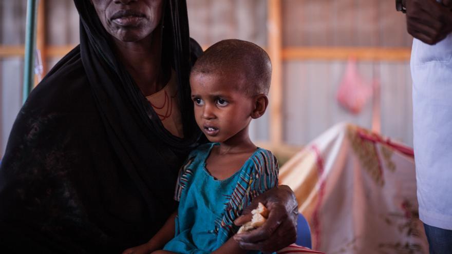 Asha (nombre ficticio), de 4 años, con su abuela Sulekha en el centro de tratamiento del cólera del hospital Bayhaw en Baidoa (Somalia). Sulekha está cuidando a su nieto mientras su hija está con los otros niños en un campamento fuera de Baidoa.