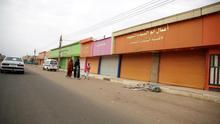 Personas caminan frente a tiendas cerradas durante el tercer día de la campaña del movimiento de desobediencia civil en Jartum, Sudán.