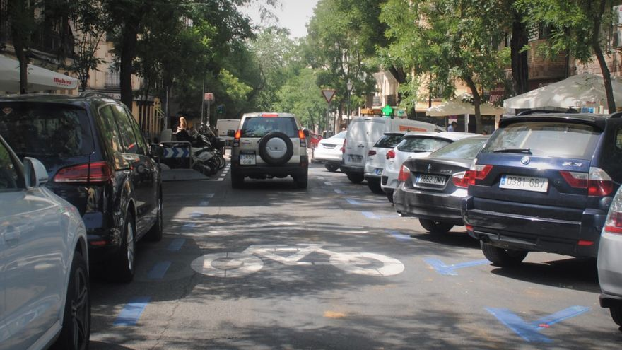 Un coche circula por la Calle Galileo entre otros vehículos aparcados en los laterales