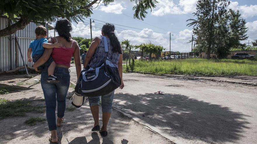 Doña Rita, madre de una reclusa, junto a su otra hija y su nieto - quien vive dentro una cárcel - caminan hacia la parada de bus, Honduras.