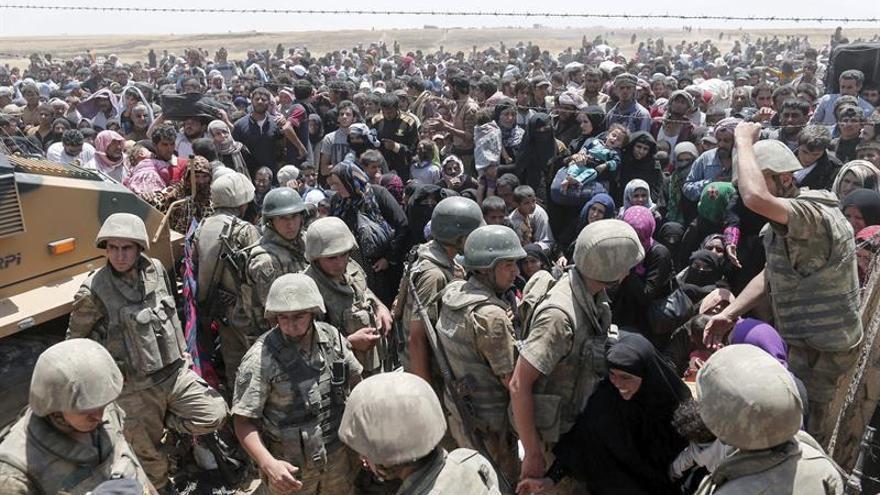 Refugiados sirios a la espera de cruzar desde su país la frontera que les separa de Turquía, cerca de Akçakale, en la provincia de Sanliurfa, Turquía.