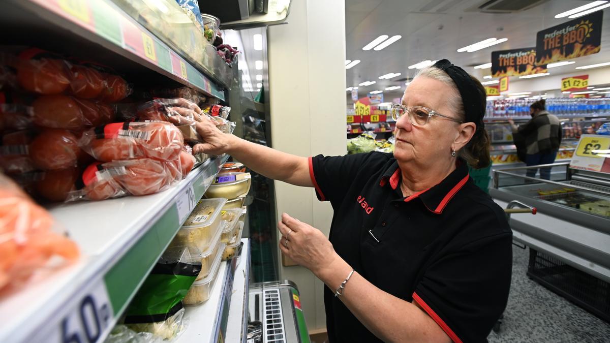Una empleada rellena una estantería en una cadena de supermercados.