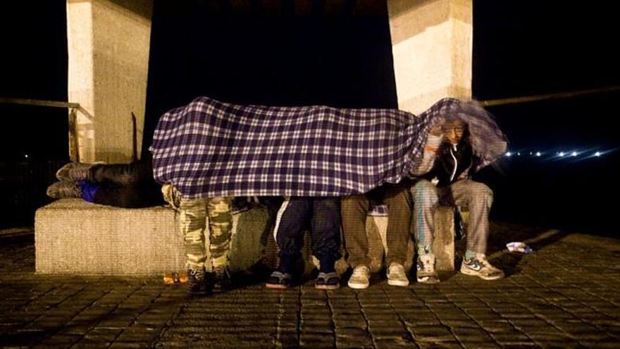 Menores extranjeros no acompañados se cubren con una manta.