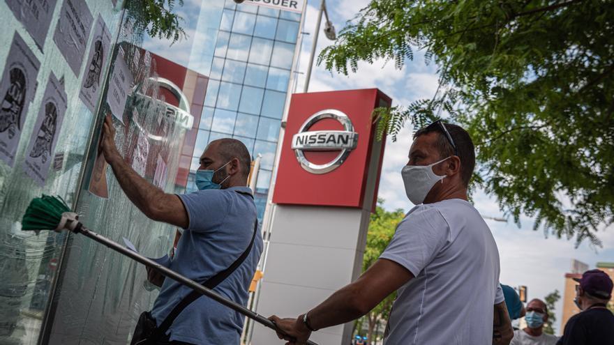 Dos trabajadores de Nissan protestan frente a la sede en Barcelona.