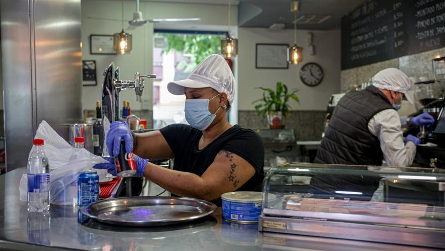 Una camarera en un restaurante preparando comida para llevar.