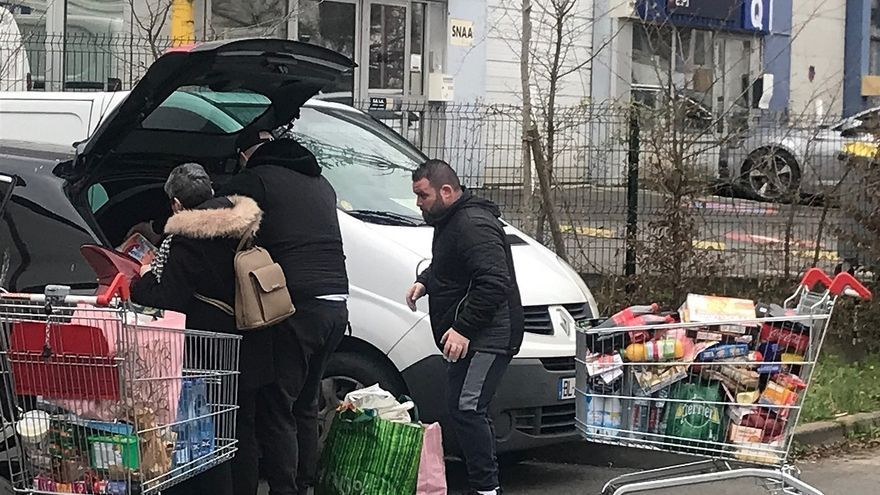 Parisinos cargan en el coche la compra durante el brote de coronavirus