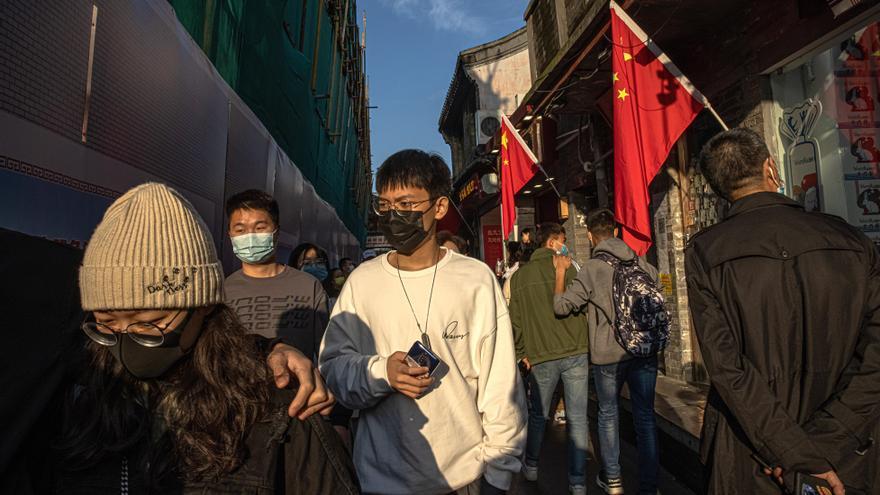 Personas con mascarillas pasan por delante de banderas durante una fiesta popular, en Pekín.
