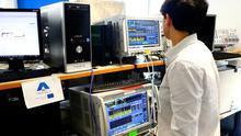 Un joven ingeniero maneja varios equipos tecnológicos.