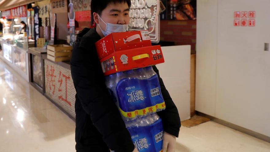Un hombre con una máscara protectora y guantes lleva bebidas y agua embotellada después de hacer la compra en un supermercado de un centro comercial en Beijing, China, 16 de febrero de 2020.