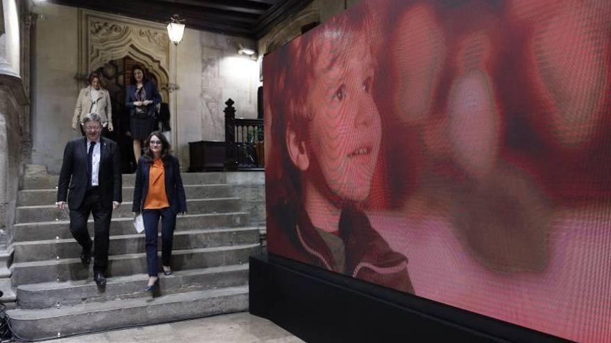 Ximo Puig y Mónica Oltra, junto a una imagen del vídeo del orgullo valenciano.