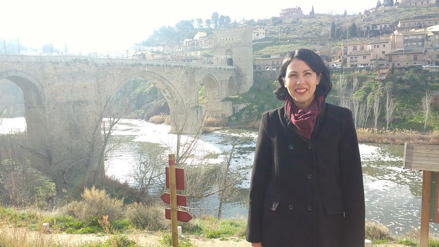 La diputada Eva García de Unidos Podemos con las espumas del Tajo en Toledo de fondo