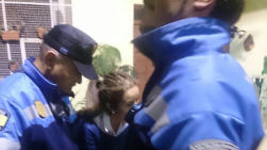 Dos policías impiden a la concejal Isabel Mena hacer fotos durante la Junta de Distrito de Tamaraceite.