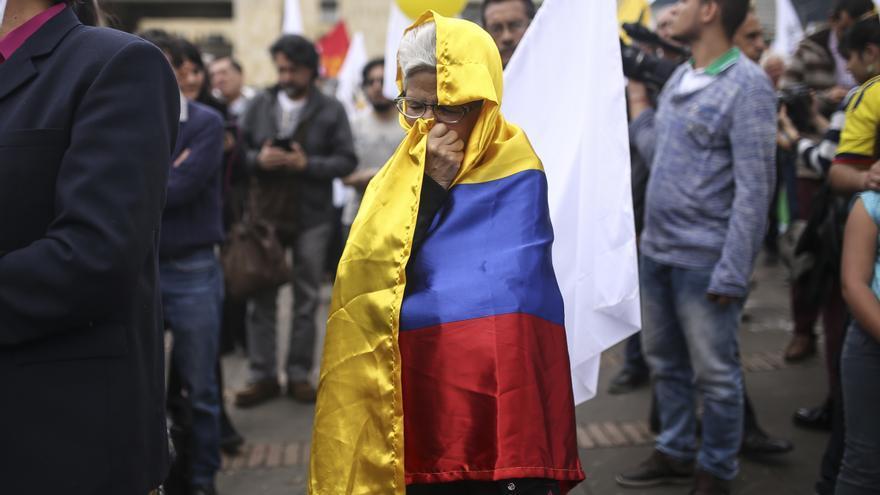 Una mujer envuelta en la bandera colombiana durante la marcha a favor del proceso de paz en Colombia © AP Photo/Ivan Valencia