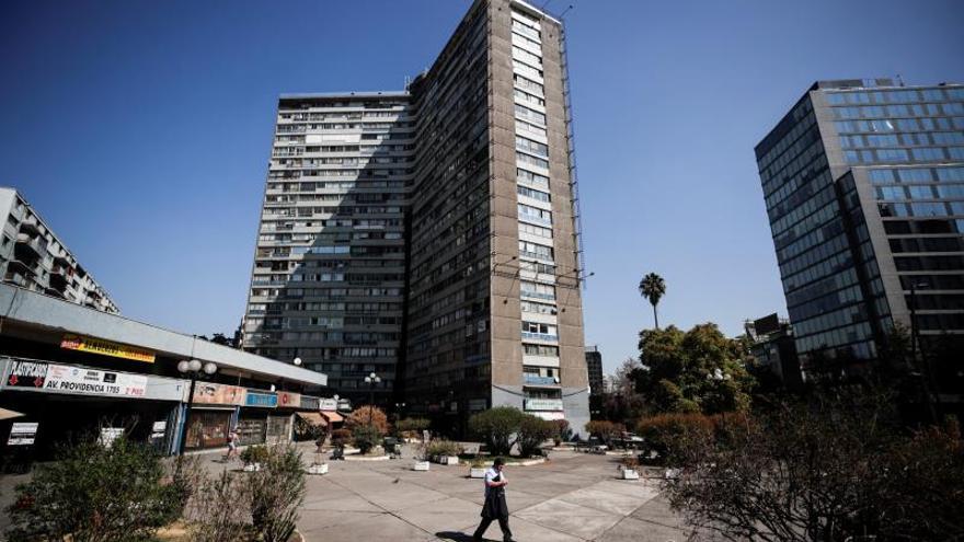 Un hombre camina frente a un edificio de viviendas en la comuna de Providencia en Santiago (Chile), EFE/Alberto Valdés/Archivo