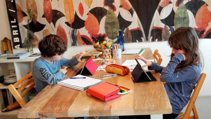"""Dos alumnos de primaria realizan las tareas escolares desde casa gracias a las tecnologías modernas que permiten la educación """"online"""" durante el estado de alarma decretado por la crisis del coronavirus."""