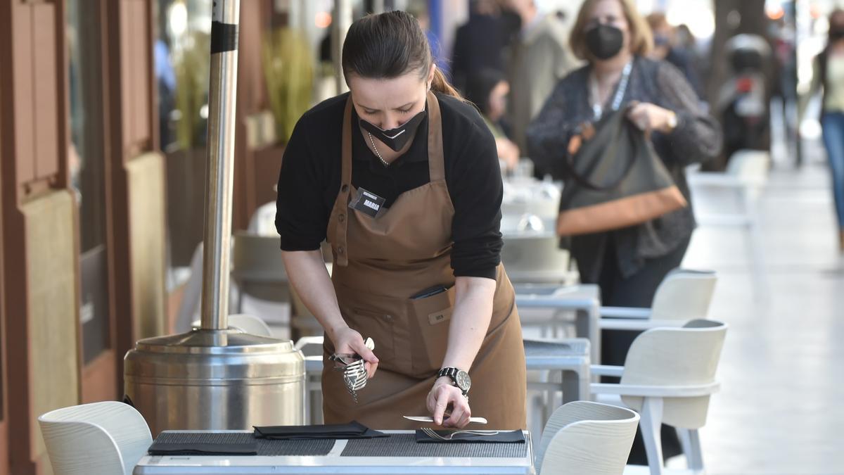 Una camarera prepara una terraza en un bar de Murcia.