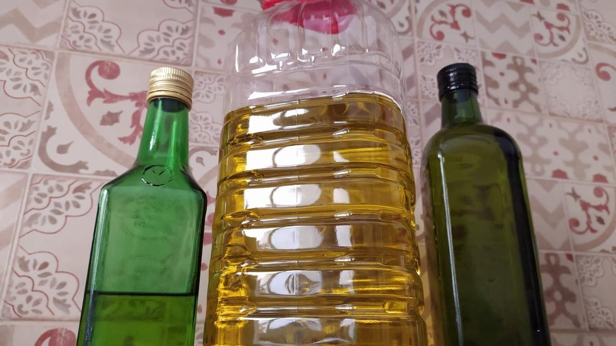 Una garrafa y dos botellas de aceite de oliva