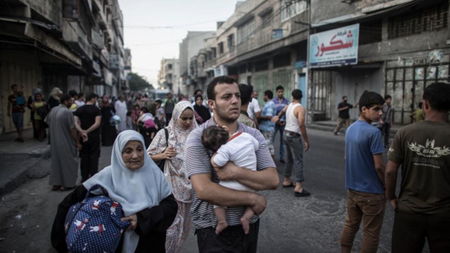 Palestinos huyendo a pie desde el barrio de Shuja'iyya, al este de la ciudad de Gaza, 20 de julio de 2014. Decenas de miles de palestinos que viven en la zona han tenido que abandonar sus casas en los últimos días para buscar refugio © EPA/OLIVER WEIKEN