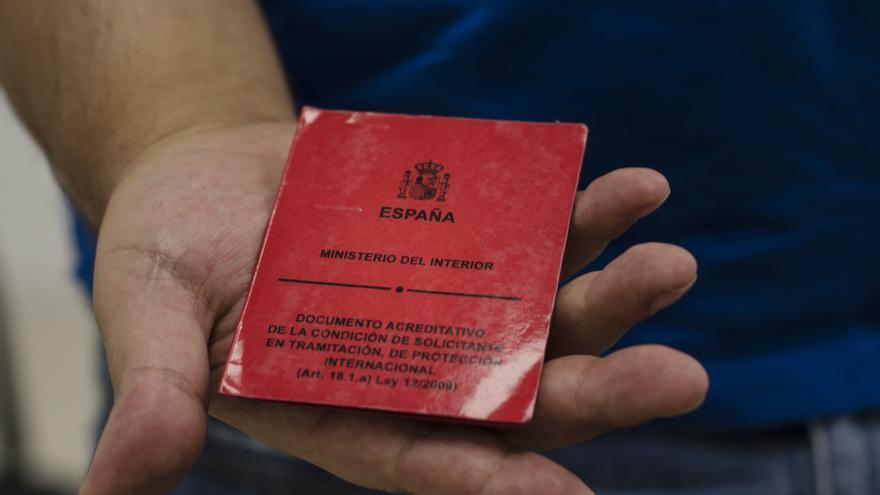 Ahmet Demir sostiene su tarjeta roja de residencia temporal