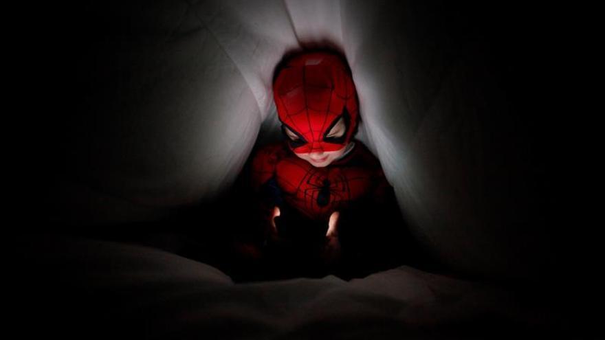 Un niño disfrazado de Spiderman se comunica mediante una videollamada con sus abuelos.