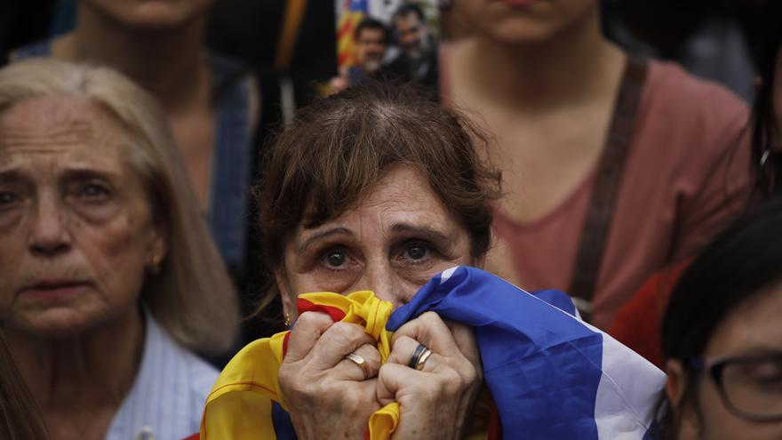 Una mujer sigue desde la calle la sesión del Parlament del viernes en la concentración de la plaza Sant Jaume.