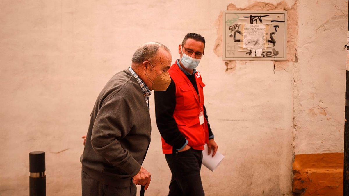 Un voluntario de Cruz Roja acompaña a una persona mayor.
