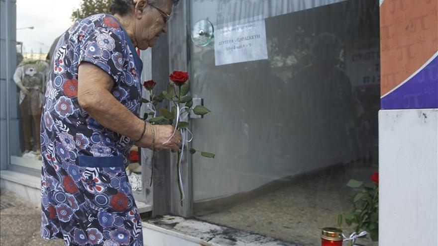 Una vecina del distrito de Keratsini deposita flores en el lugar en el que Fyssas fue asesinado.
