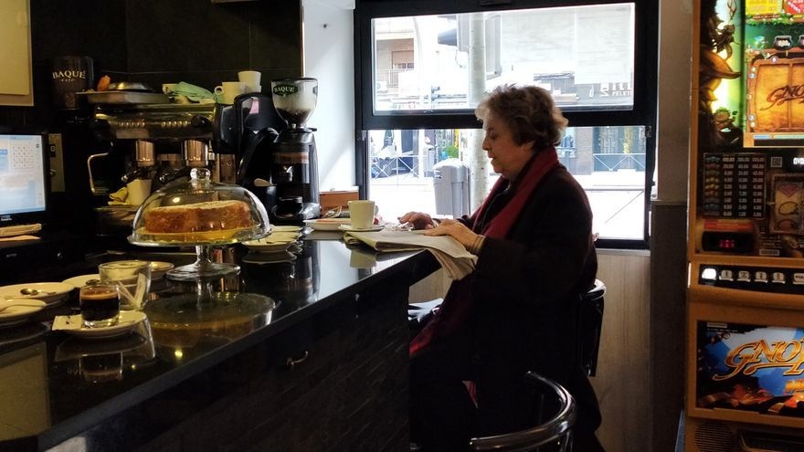 Una mujer lee la prensa en un bar sobre la calle General Ricardos, en Carabanchel (Madrid).