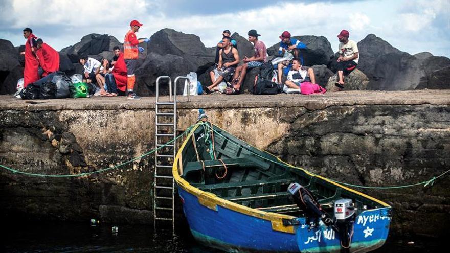 Un barco pesquero remolca al puerto de La Santa, en Tinajo (Lanzarote), a una patera en la que viajaban 30 personas. EFE/JAVIER FUENTES.