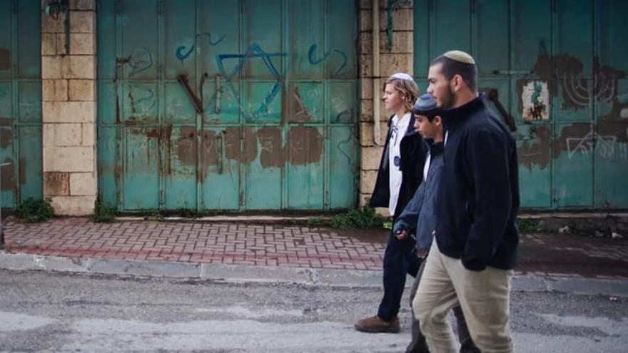 Colonos israelies pasan por delante de un antiguo comercio palestino marcado con la Estrella de David mientras caminan por la calle principal de la ciudad antigua de Hebrón.