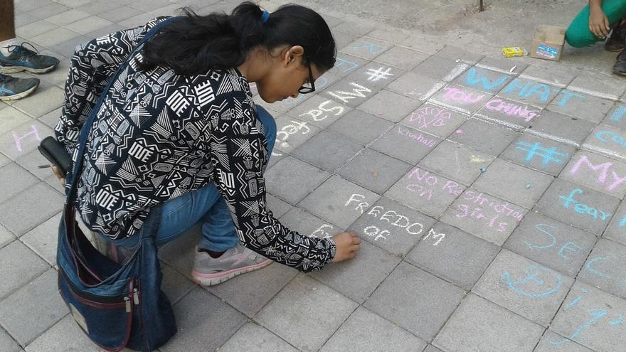Un chica pide con tiza en el suelo libertad / Anti-Street Harassment
