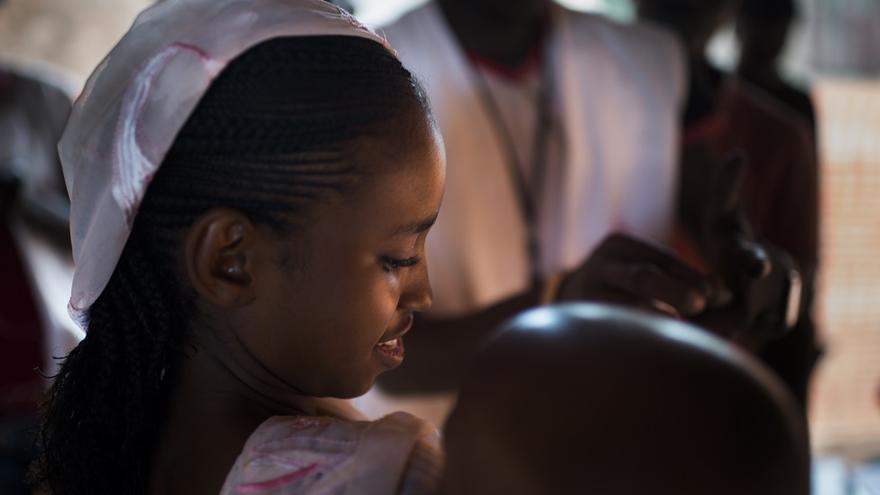 La madre de Madina, de 12 meses de edad, lleva al menor al centro de vacunación junto a su madre.