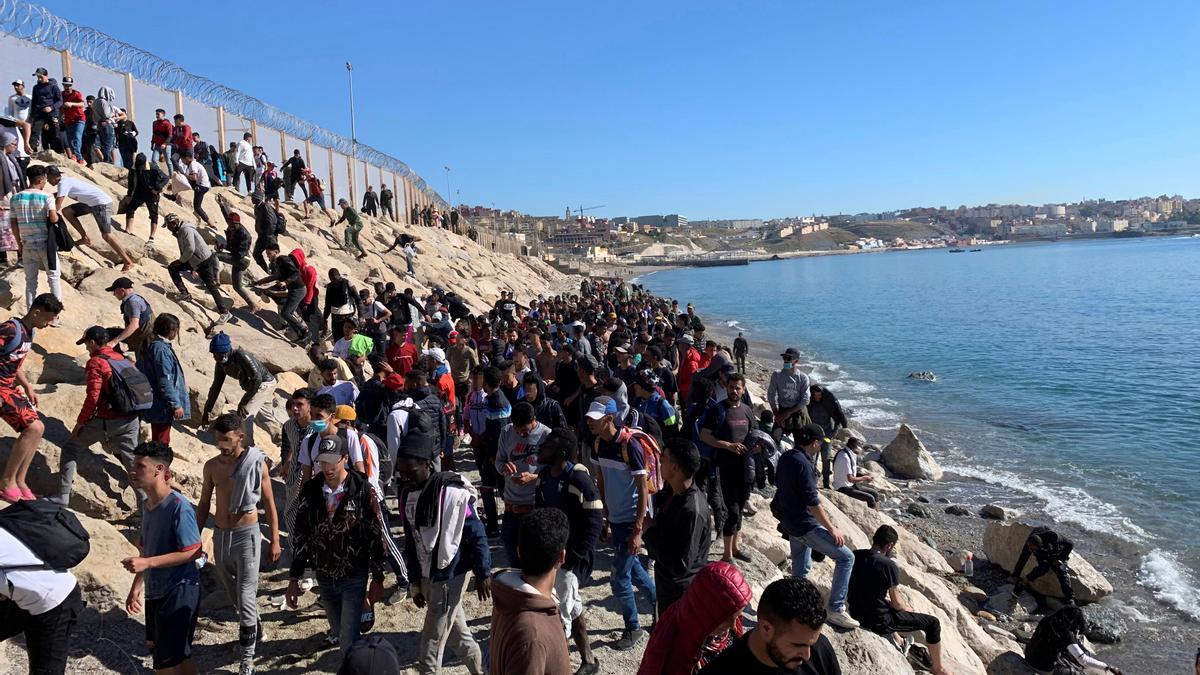 Un grupo de personas tratan de cruzar la valla fronteriza que separa Fnideq (Castillejos, Marruecos) y Ceuta este miércoles, tras la llegada de hasta 8.000 inmigrantes a Ceuta y Melilla en los dos últimos días. EFE/ Mohamed Siali