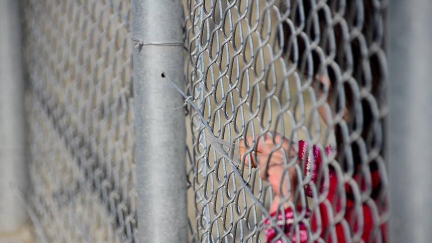Una niña siria intenta cortar la alambrada del centro de detención en el que está encerrada en la isla griega de Quíos.   Imagen cedida por el activista Benjamin Julian