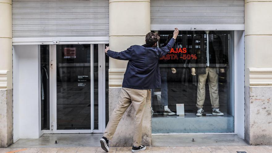 Un trabajador cierra su establecimiento el primer día del cierre total de la hostelería y de tiendas a las 18.00h en Valencia