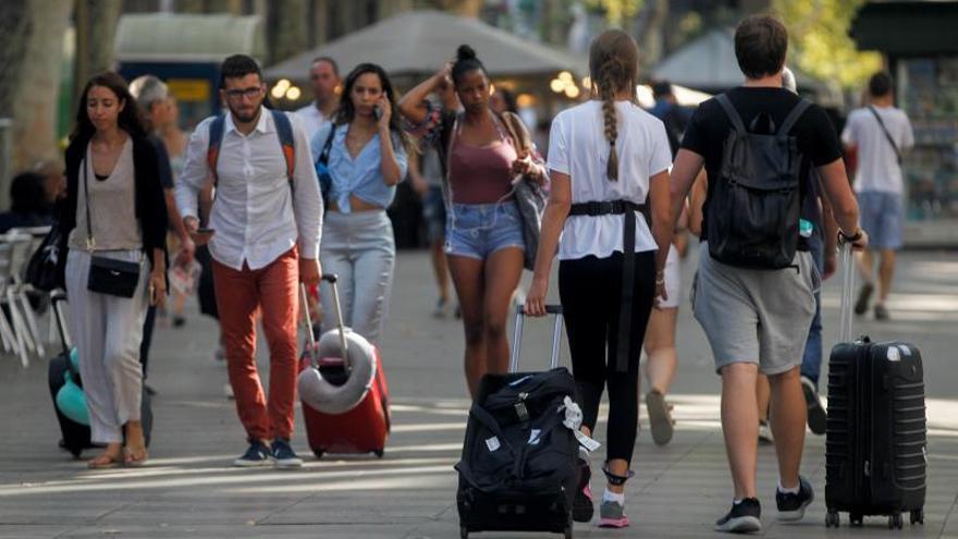 Turistas caminando por La Rambla de Barcelona.