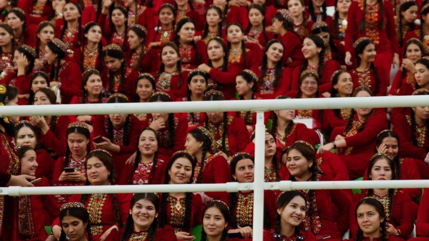 Universitarias turkmenas, vestidas con el uniforme oficial, aguardan el inicio de un acto patriótico.