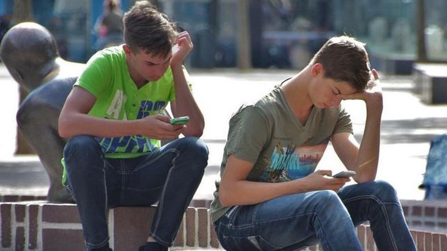 Jóvenes en la calle, absortos en sus teléfonos móviles