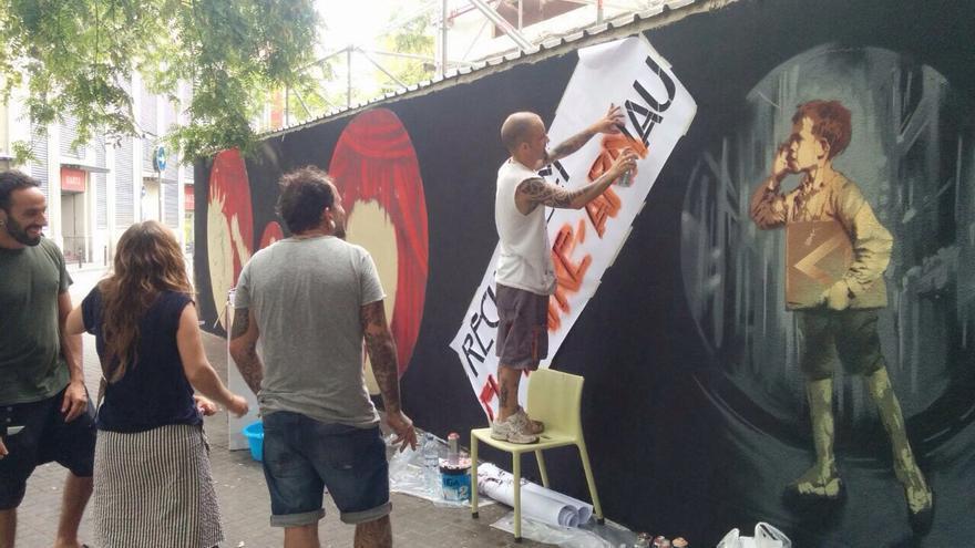 'Recuperem l'Arnau per al veïnat', lema del mural reivindicativo que luce el viejo teatro / Salvem l'Arnau