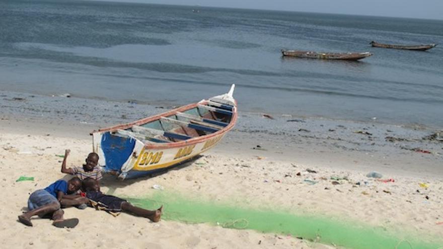 Unos niños saludan junto a un cayuco en una playa de Thiaroye (Senegal).