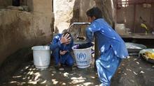 Dos refugiados afganos de tercera generación juegan en un pozo de agua, el pasado 4 de julio en el campo de Kababian, en el noroeste de Pakistán | FOTO: EFE
