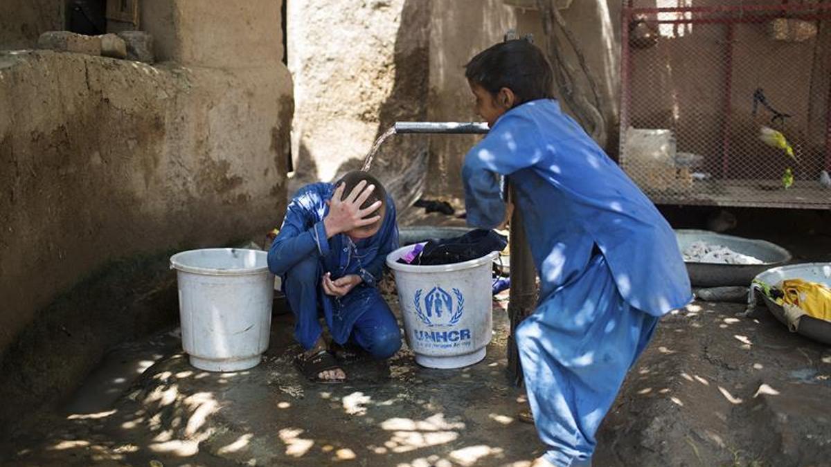 Dos refugiados afganos de tercera generación juegan en un pozo de agua, el pasado 4 de julio en el campo de Kababian, en el noroeste de Pakistán.