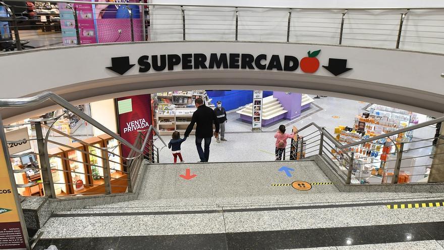 Varias personas realizan sus compras en un centro comercial.