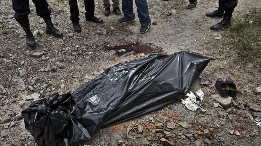El doctor Abullarade, polícias de laboratorio criminalístico y un fiscal, hablan cerca del cadáver de un joven en Mexicanos, un municipio cercano a San Salvador./Edu Ponces (RUIDO Photo)